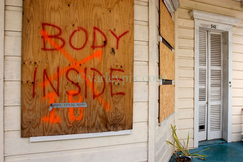 07 Oct, 2005.  New Orleans, Louisiana. Hurricane Katrina aftermath.<br /> 'Body Inside.' The stark spray paint on the outside of a house in Uptown New Orleans. A tape attached to the panel reads 'Removed 9.19.05 Kenyon.' Kenyon are the private contractors hired by the city to pick up corpses left behind after the storm. <br /> Photo; ©Charlie Varley/varleypix.com