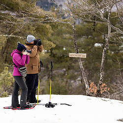 A man and woman do some winter photography near the summit of Bald Pate Mountain at Loon Echo Land Trust's Bald Pate Mountain Preserve in South Bridgton, Maine.