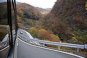 tour bus driving downhill on a mountain pass in autumn season Okunikko mountain range Japan