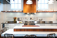 A contemporary kitchen in Urbana Kitchens showroom in Victoria, BC features bookended walnut on the hood fan cover, white Cambria quartz counters and a stainless Bertazzoni gas range.