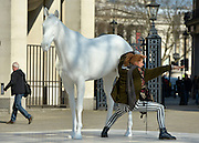 © Licensed to London News Pictures. 05/03/2013. Westminster, UK A tourist poses for a photograph with the new sculpture. The British Council - the UK's international organisation for educational opportunities and cultural relations - unveils a new sculpture, The White Horse by Mark Wallinger, outside its headquarters on The Mall in London, as it announces £7 million of extra investment in its work to connect the best of the UK's creative talent with the world. The statue, made of marble and resin, is a life-size representation of a thoroughbred racehorse. It has been created using state-of the-art technology in which a live horse was scanned using a white light scanner, producing an accurate representation of the animal. It will be on display for two years, before touring overseas. Photo credit : Stephen Simpson/LNP