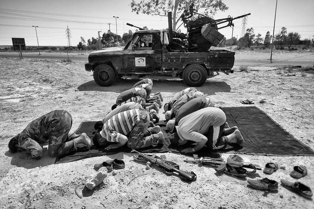 Libye, Syrte le 19-09-11 Les rebelles qui tentent de prendre le contrôle de la ville de Syrte, bastion pro Kadhafi se heurtent à une résistance qui les obligent à battre en retraite. des combattants font une prière avant d'aller sur la ligne de front.