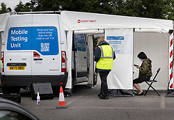© Licensed to London News Pictures. 19/06/2021. Tattenham Corner, UK. A local resident (R) takes a PCR covid-19 test at a mobile test centre at Tattenham Corner, Surrey. Surge testing for the coronavirus is taking place in parts of Surrey after a rise in infections caused by the delta variant. Photo credit: Peter Macdiarmid/LNP