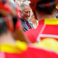Prince Charles greets bicycle athletes from many countries at the starting line of the 250 km road race from The Mall, near Buckingham Palace, during the 2012 London Summer Olympics.