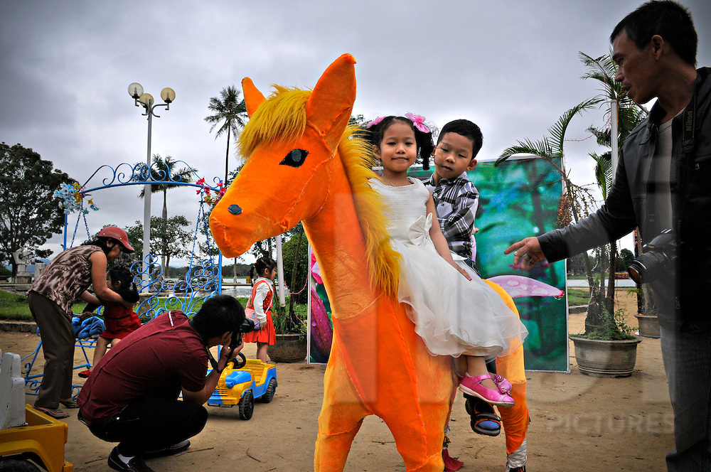 Two Vietnamese kids play on a fake orange horse in a park near the Perfume River in Hue, Vietnam, Southeast Asia