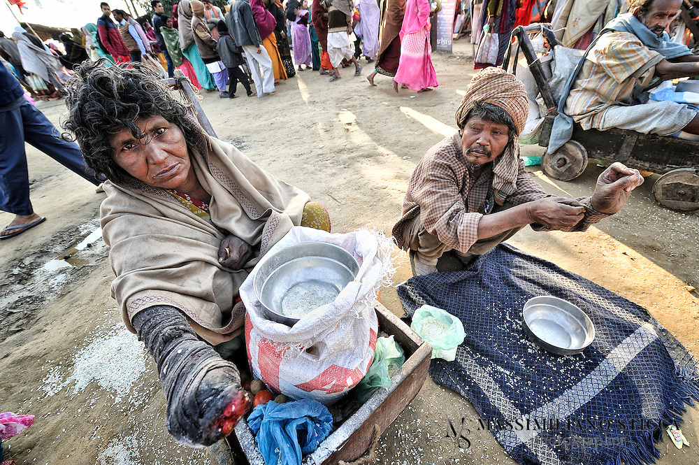 A leper (sx) and a beggar (dx) ask charity near the river Ganges.
