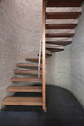 wooden staircase with grey brick wall