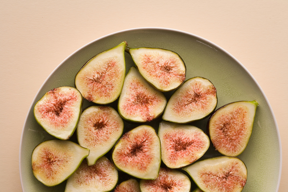 Birds eye view of sliced juicy red centred fresh figs on a green plate