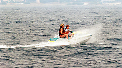 Diana, Princess of Wales, wearing a swimsuit, rides with Prince Harry on a jet ski in 1996 off the coast of the South of France. Anwar Hussein/EMPICS Entertainment