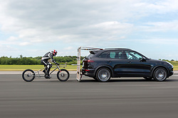 © Licensed to London News Pictures. 18/06/2018. York UK. 42 year old architect Neil Campbell has achieved a new unofficial European bicycle speed record this afternoon by reaching 129mph on his £10,000 custom built bicycle at Elvington airfield in York ahead of his world record attempt tomorrow. Neil is the holder of the British & Commonwealth bicycle speed record of 114mph. Neil gets up to speed behind a Porsche before being released for him to take over under his own pedal power. The world record attempt will take place tomorrow as part of the Straightliners event on Elvington airfield.  Photo credit: Andrew McCaren/LNP