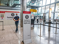 © Licensed to London News Pictures. 20/10/2020. London, UK. A Heathrow worker walks past a testing centre at Heathrow Terminal 5. A one hour Covid-19 testing centre at London Heathrow for Hong Kong and Italy passengers has opened up at London Heathrow. Two facilities one at Terminal 5 and the other at Terminal 2 will offer much quicker results than the NHS as samples don't need to be sent away to be tested. Prime Minister Boris Johnson is expected to announce a Tier 3 lockdown for Manchester tonight as coronavirus levels of infections continue to escalate throughout the UK. Photo credit: Alex Lentati/LNP