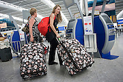 "A slightly comical scene of modern air travel as two lady passengers haul matching suitcases at the British Airways self-check-in kiosk at Heathrow Airport's Terminal 5. The self-service kiosks that have been developed to allow customers to process their own ticketing on arrival at this aviation hub for British Airways. Once they've chosen their seat and printed a boarding pass, they can go straight to the Fast Bag Drop desk at the airport. There, baggage will be tagged by an agent and sent to the aircraft. At a cost of £4.3 billion, Terminal 5 has the capacity to serve around 30 million passengers a year. From writer Alain de Botton's book project ""A Week at the Airport: A Heathrow Diary"" (2009). ..."