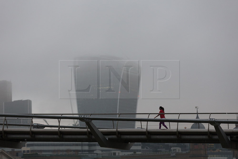 © Licensed to London News Pictures. 07/01/2017. LONDON, UK.  A woman walks over Millennium Bridge, with the Walkie Talkie skyscraper behind shrouded in mist and fog. The weather in London today is misty, foggy and much milder than it has been during the past week.  Photo credit: Vickie Flores/LNP
