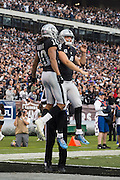 Oakland Raiders wide receiver Seth Roberts (10) and Oakland Raiders quarterback Derek Carr (4) celebrate a touchdown against the Buffalo Bills at Oakland Coliseum in Oakland, Calif., on December 4, 2016. (Stan Olszewski/Special to S.F. Examiner)
