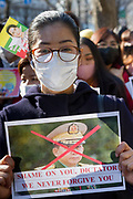 A woman holds a crossed out poster of General Min Aung Hlaing, the nominal aleader of the military coup  as thousands of Japanese and Myanmar nationals protest outside the Japanese Foreign Ministry in Tokyo calling for the Japanese government to take action over the recent coup in Myanmar. Kasumigaseki, Tokyo, Japan. Wednesday February 3rd 2021, Many of the protesters held flags of Aung San Suu Kyi's National League for Democracy (NLD), along with portraits of the the detained leader herself and former President, Win Myint.