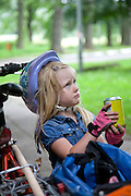 Unhappy Polish girl age 4 with soda wearing pink fingerless bicycle gloves and helmet. Paderewski Park Rzeczyca Central Poland