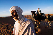 Elhussein Sbiti leads an American client on a three-day camel trek to the remote dunes of Erg Zehar, near M'hamid in the Moroccan Sahara. Sbiti, like many berber nomads in the region, has found opportunity in the new tourism trade burgeoning since the settling of tensions between Morocco and neighboring Algeria.