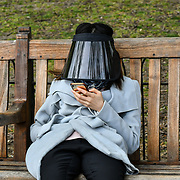A Asian girl wearing a fashion face shield sitting at St James park and a lovely weather on 23 April 2019, London, UK.