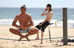 Two strapliners practice on Bournemouth beach in Dorset as forecasters predict that a wave of warm air will move across the country in the coming days.