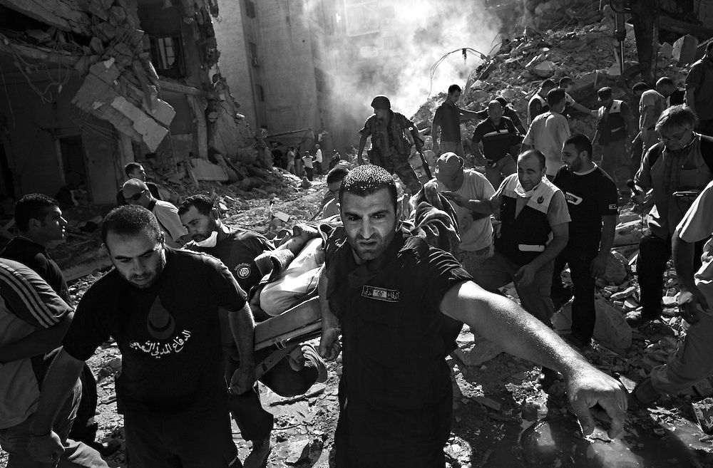 Lebanese civil defense workers remove bodies from an Israeli airstrike in the residential neighborhood of Chiyah, which killed more than two dozen people and wounded scores more, in Beirut, Lebanon, Aug. 8, 2006.