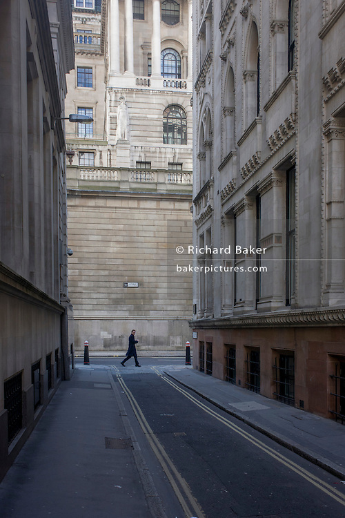 A lunchtime pedestrian on the corner of Lothbury and Tokenhouse Yard, two narrow and historic streets with the high walls of the Bank of England in the background -  in the City of London, the capital's financial district. The area was populated with coppersmiths in the Middle Ages before later becoming home to a number of merchants and bankers. Lothbury borders the Bank of England on the building's northern side. Tokenhouse St dates from Charles I and was where farthing tokens were coined. The City of London is the capital's historic centre first occupied by the Romans then expanded during following centuries until today, it has a resident population of under 10,000 but a daily working population of 311,000.