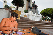 Sept. 23, 2009 -- BANGKOK, THAILAND: A homeless man makes flower garlands he sells to visitors of the King Rama I statue at the foot of Memorial Bridge in Bangkok. The homeless camp has been there for about 20 years. Most of the people who live there are children and teenagers ages 10 - 20. Photo by Jack Kurtz / ZUMA Press