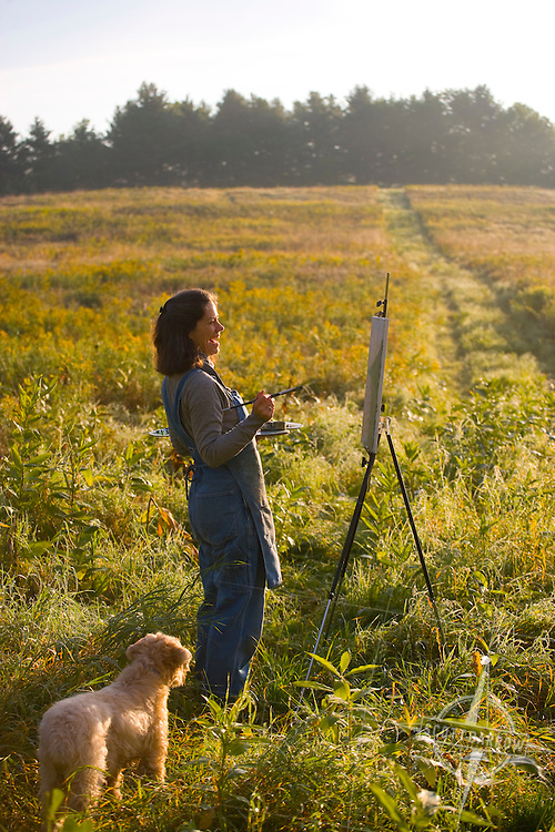 Female painter in field in early morning with her dog.