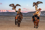 Kazakh eagle hunters hunting in the Altai mountains with their golden eagles on horseback at dusk during a full moon, Altai Mountains, Bayan Ulgii, Mongolia