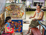 27 JUNE 2015 - BANGKOK, THAILAND:   An artist paints a portrait of a girl in front of his studio on Khlong Bang Luang. The Bang Luang neighborhood lines Khlong (Canal) Bang Luang in the Thonburi section of Bangkok on the west side of Chao Phraya River. It was established in the late 18th Century by King Taksin the Great after the Burmese sacked the Siamese capital of Ayutthaya. The neighborhood, like most of Thonburi, is relatively undeveloped and still criss crossed by the canals which once made Bangkok famous. It's now a popular day trip from central Bangkok and offers a glimpse into what the city used to be like.       PHOTO BY JACK KURTZ