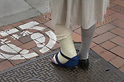 girl with broken leg standing and waiting at a stop painted street sign pedestrian crossing in Tokyo Japan