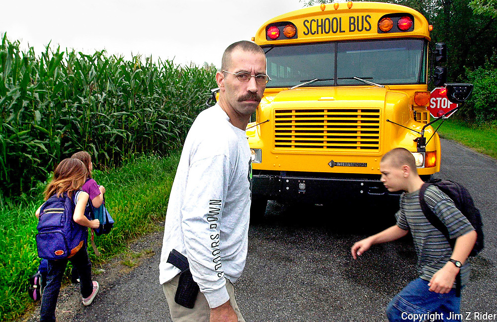 Richard Loy, then Grand Dragon of the Indiana Knights of the Klu Klux Klan, escorts his children on to a school bus with a loaded pistol strapped to his hip.  Loy asked the Penn Harris Madison School Corporation, Mishawaka, Indiana, not to seat his children next to minorities on the bus.  The corporation declined his request.  Loy and his father, both leaders of the Indiana KKK, have held several rallies on their rural property in Osceola, Indiana.  Neighbors have taken the Loy family to court, filing charges of intimidation.