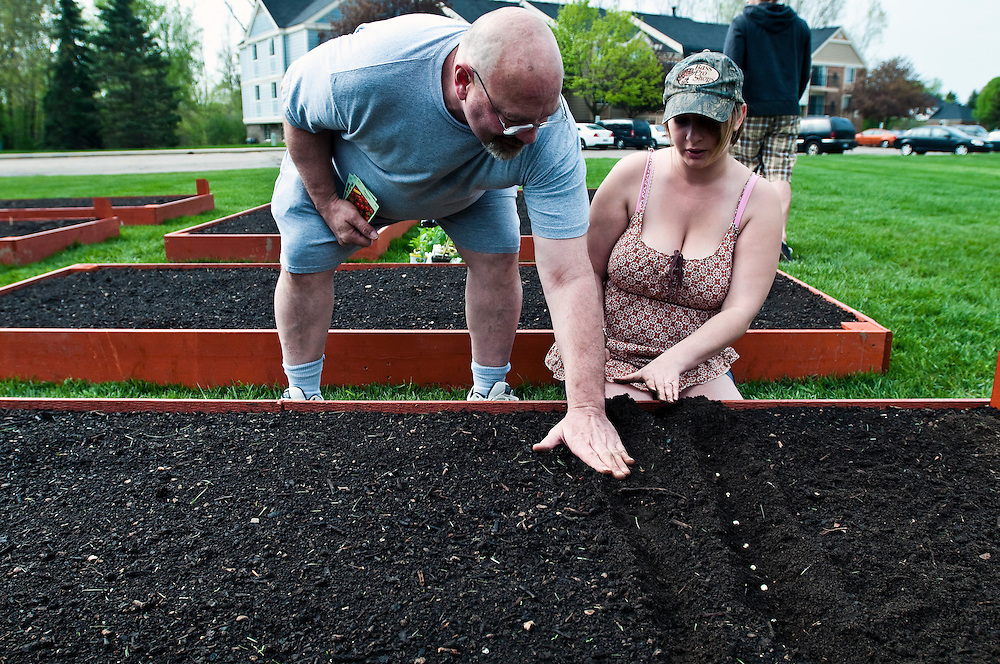 Matt Dixon   The Flint Journal..Tom Cartell, 52 plants pea seeds with neighbor Tessa Ruff, 18, at Charter Oaks Apartments in Davison Thursday morning. The two decided to share one of several 4-feet-by-10-feet garden plots which were recently installed for residents to rent.
