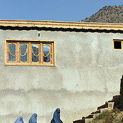 Women in burqas leave a girl's school in the village of Nari, Kunar Province of Eastern Afghanistan after a water filter demonstration with Waves For Water and the US Military.