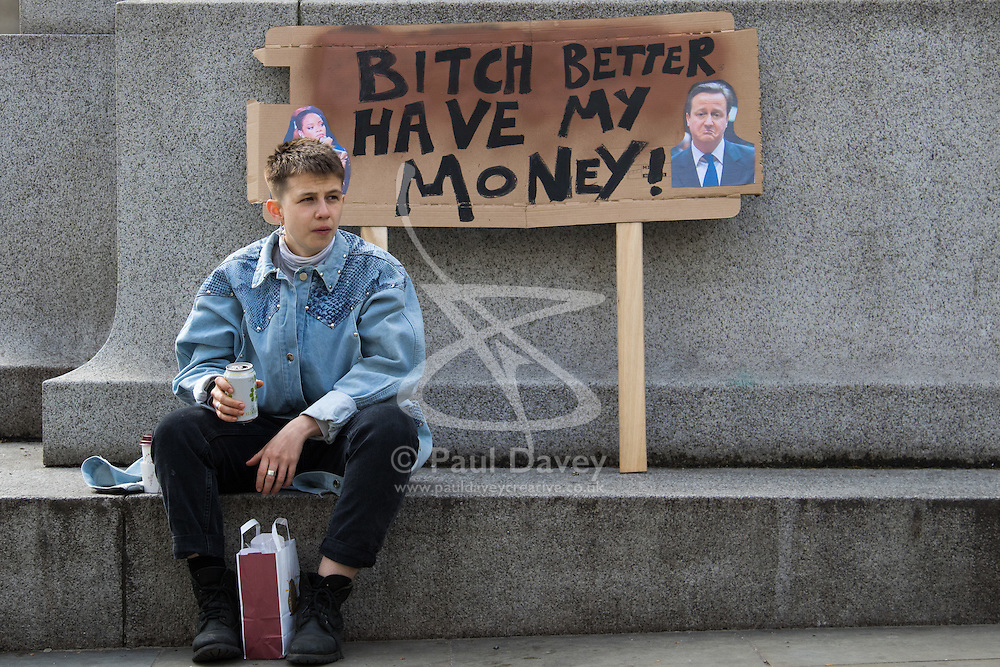 """London, April 16th 2016. A youngster sits in front of a discarded banner after thousands of people supported by trade unions and other rights organisations demonstrated against the policies of the Tory government, including austerity and perceived favouring of """"the rich"""" over """"the poor""""."""