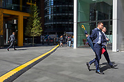 A lunchtime office worker crosses a yellow line covering hazardous electrical cabling at Leadenhall in the City of London, (aka The Square Mile) the capital's financial district, on 2nd September 2019, in London, England.