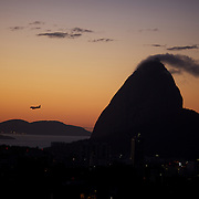 A passenger airline jet  prepares to land as the sun rises behind the summit of Sugar Loaf Mountain, one of the iconic locations with breathtaking views of Rio de Janeiro, Brazil. 26th July 2010. Photo Tim Clayton.