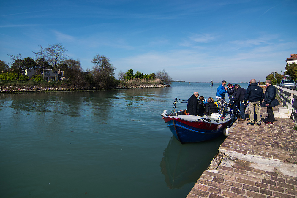 """VENICE, ITALY - APRIL 2018. <br /> Tourists get on the boat to start the fishing tour of moeche. The tour is leaded by Sebastiano, a fisherman that lives in the island of Burano. The tour will end eating some fresh moeche in a """"cason"""", the typical temporary house of the fishermen of the Venetian lagoon, but just after visiting a moecante (crabs fisherman) while working."""