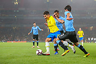 Uruguay defender Bruno Mendez (3) and Uruguay defender Matias Vecino (13) attempt to stop Brazil forward Roberto Firmino (20) during the Friendly International match between Brazil and Uruguay at the Emirates Stadium, London, England on 16 November 2018.