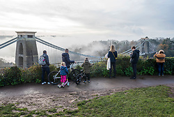 © Licensed to London News Pictures; 22/11/2020; Bristol, UK. People look and take photographs of the Clifton Suspension Bridge over the Avon Gorge with mist during the Covid-19 lockdown in England during the coronavirus pandemic as the UK Government tries to stop the spread of the covid-19 coronavirus pandemic. Bristol now has one of the highest rates of Covid-19 infection in the country. Photo credit: Simon Chapman/LNP.