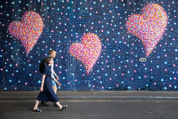 © Licensed to London News Pictures. 03/06/2018. London, UK. A man and woman walk past a heart mural near Borough Market, on the anniversary of the London Bridge and Borough Market terror attack. A series of events are taking place throughout the day, including a service of commemoration at Southwark Cathedral, the planting of an olive tree in the Cathedral grounds, a minute's silence at 4:30pm and the laying of flowers.  Photo credit : Tom Nicholson/LNP