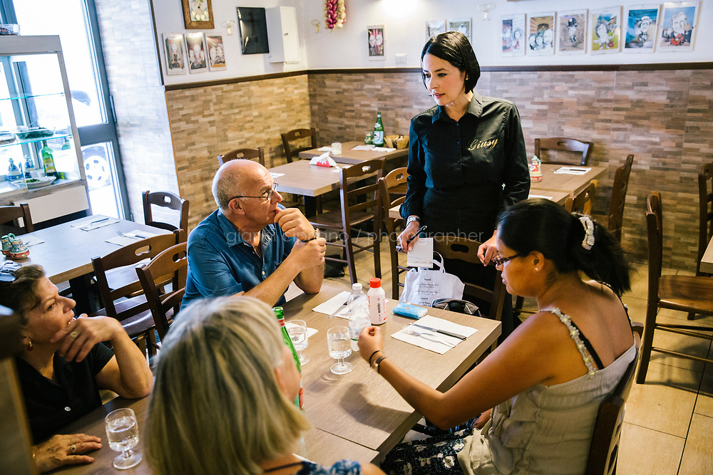 """NAPLES, ITALY - 12 SEPTEMBER 2018: Giusy Aiese, co-owner of the Taverna del Buongustaio, takes orders from customers, in Naples, Italy, on September 12th 2018.<br /> <br /> Taverna del Buongustaio was founded in the 1930s by wine producer of the province of Caserta. Gaetano Aiese and his daughter Giusy have been managing the tavern since 1996. Customers of the Taverna are professors of the nearby University, students, merchants and employees of via Toledo, the commercial street right around the corner. Giusy and her father Gaetano decided to invest in the traditional Neapolitan cuisine. """"I learned cooking from my dad. And my dad learned cooking from his mother"""", Giusy said."""
