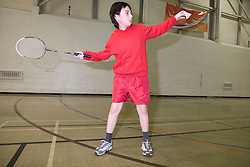 Young boy playing a game of badminton in the sports hall of his local leisure centre,