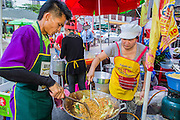 17 OCTOBER 2012 - BANGKOK, THAILAND:  Vendors make vegan Chinese style noodles at the Vegetarian Festival food fair on Yaowarat Road in Chinatown in Bangkok. The Vegetarian Festival is celebrated throughout Thailand. It is the Thai version of the The Nine Emperor Gods Festival, a nine-day Taoist celebration celebrated in the 9th lunar month of the Chinese calendar. For nine days, those who are participating in the festival dress all in white and abstain from eating meat, poultry, seafood, and dairy products. Vendors and proprietors of restaurants indicate that vegetarian food is for sale at their establishments by putting a yellow flag out with Thai characters for meatless written on it in red.      PHOTO BY JACK KURTZ