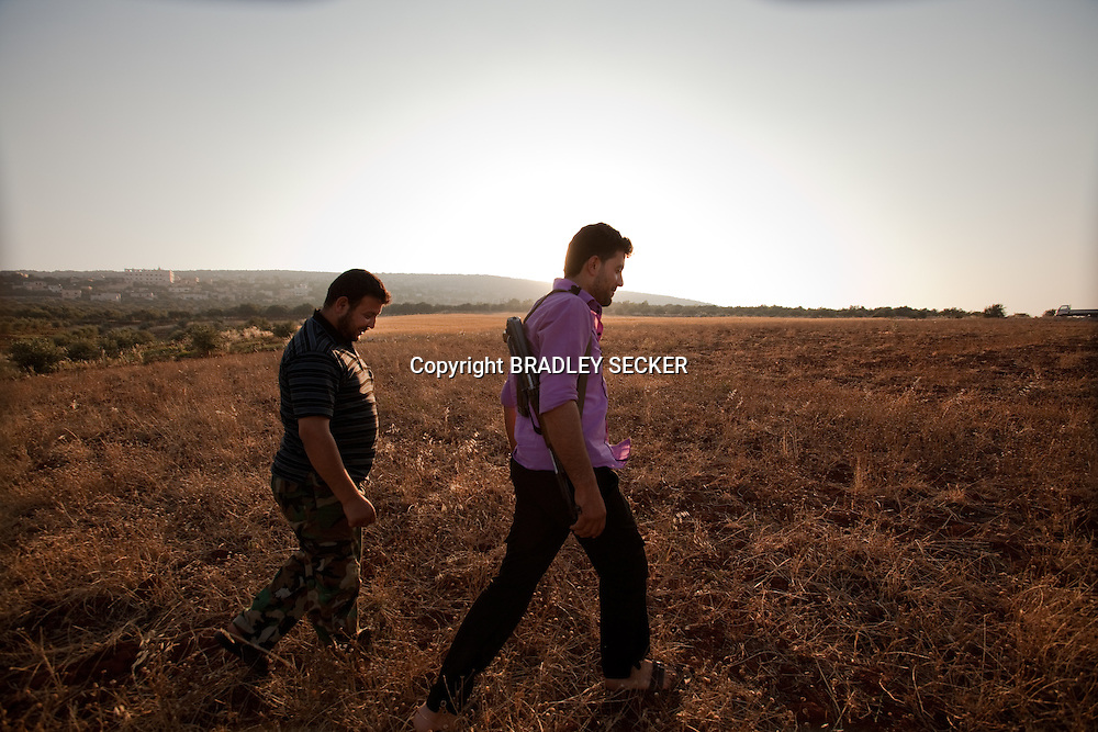 An FSA soldier walks through a field surrounding the town of Basheria, Idlib province in Syria's northwest. Idlib province in Syria's northwest is one of the few areas in Syria which is currently under FSA control, although this control is patchy and ever shifting. al-Basheria, Idlib, Syria. 19/06/2012