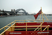 Top-deck seating of Sydney Harbour Ferry, with Sydney Harbour Bridge in background. All Sydney Harbour Ferries fly the Red Ensign, Australia's official Maritime flag. Sydney, Australia
