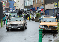 © Licensed to London News Pictures; 21/02/2021; Bristol, UK. Cars with licence plates from the 1960s to the 1980s are seen as filming takes place in East Street in Bedminster for Extinction, a Sky Original eight-part series produced by Urban Myth Productions in association with Sky Studios. This scene is set in the latter part of the 20th century with period cars and some generic shop fronts. The main character George is played by Paapa Essiedu, who rose to fame following his role as Kwame in BBC drama I May Destroy You. Extinction follows the story of George as he begins to re-live time after witnessing the end of the world. Film crew are seen wearing PPE during the coronavirus pandemic, along with extras who wear masks in between takes. Photo credit: Simon Chapman/LNP.