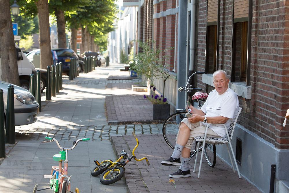 Een man zit voor zijn huis in het Limburgse Eijsden.<br /> <br /> A man sits outside his home in Eijsden.