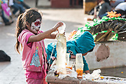 A young girl with her face painted for the Day of the Dead festival plays with water from a fountain in the town plaza in Opopeo, Michoacan, Mexico.