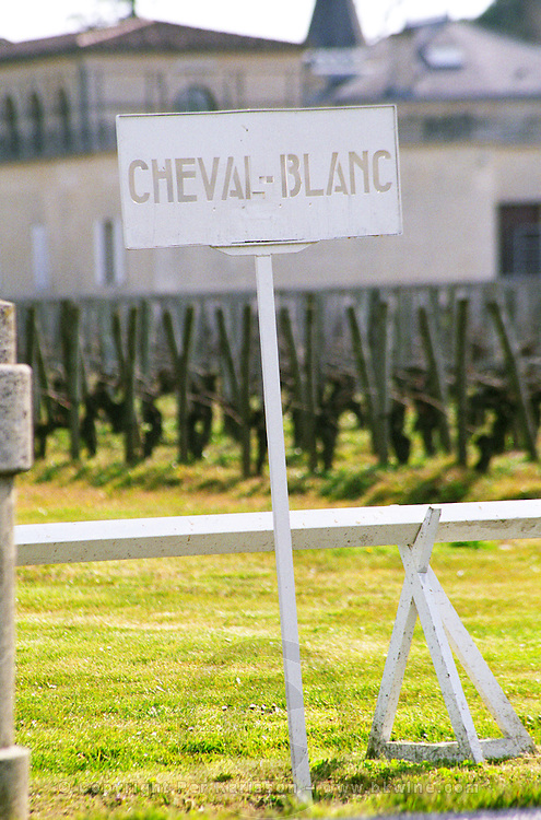 The vineyard and chateau of Chateau Cheval Blanc. A white painted sign in the vineyard saying Cheval Blanc (The White Horse) with the chateau in the background in early spring. Château Cheval Blanc, Saint St Emilion Emilion, Bordeaux Gironde Aquitaine France Europe