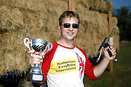 Photo by Andrew Tobin/Tobinators Ltd - 07710 761829 - 2013 World Champion Rob Bresler celebrates during the World Peashooting Championships held at Witcham, Cambridgeshire, UK on 13th July 2013. Run in conjunction with the village fair, the Championships have been held in Witcham since 1971 when they were started by a Mr Tyson, the village schoolmaster, in order to raise funds for the village hall.Competitors come from as far afield as the USA and New Zealand to attempt to win the event. The latest technology is often used, including laser sights and titanium and carbon fibre peashooters. All peashooters must conform to strict length rules, not exceeding 12 inches, and have to hit a target 12 feet away. Shooting 5 peas at a plasticine target attached to a hay bale, the highest scorers move through the initial rounds to a knockout competition, followed by a sudden death 10-pea shootout.
